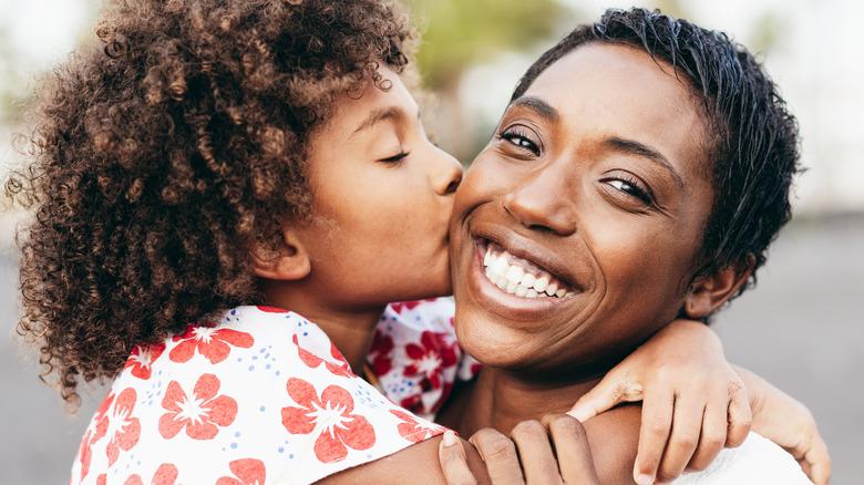 Child kissing mom on the cheek