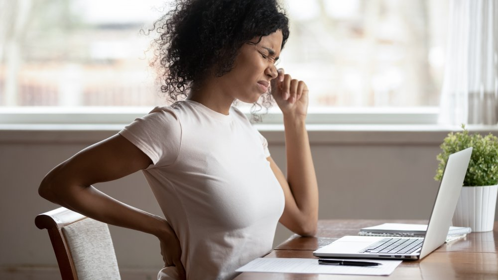 Twentysomething woman at a desk wincing from lower back pain