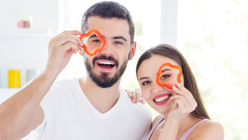 man and woman holding up pepper slices