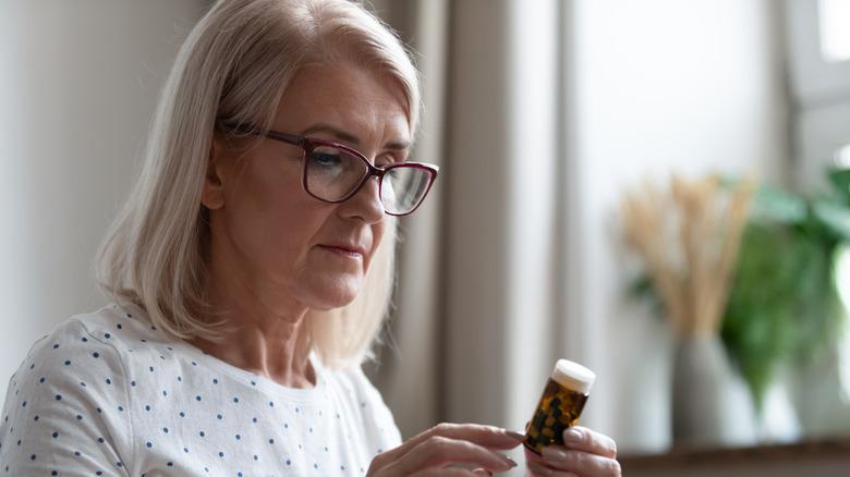 woman reading pills label