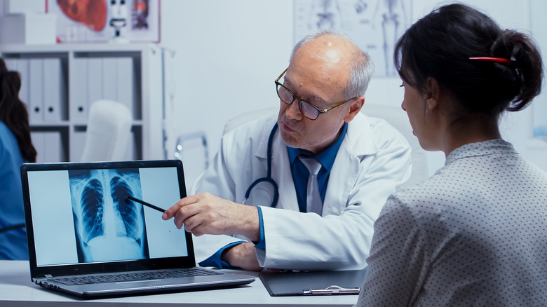 doctor showing lung X-ray to patient