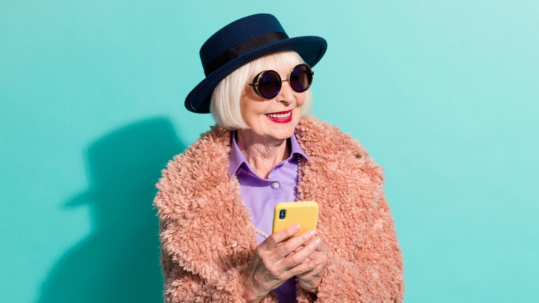 stylish older woman wearing a blue hat and textured pink jacket