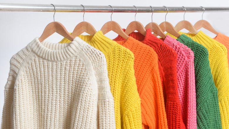 Colorful knitted sweaters hanging on a rack