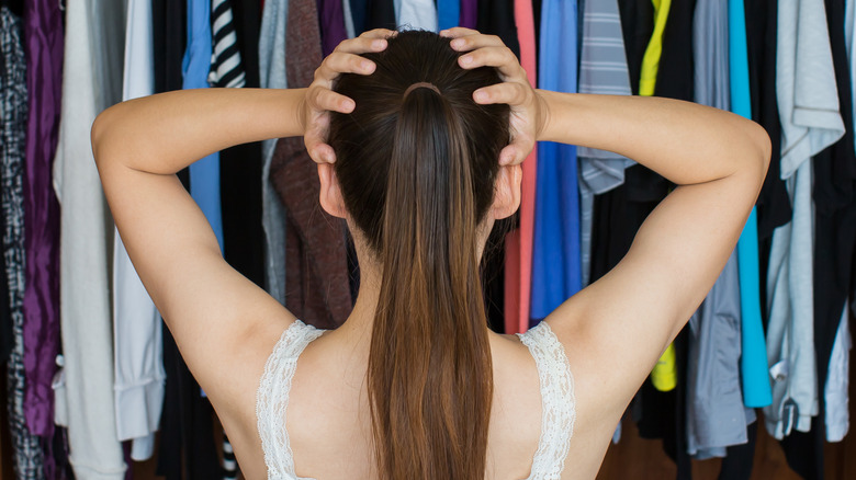 photo of a frustrated woman in front of her closet