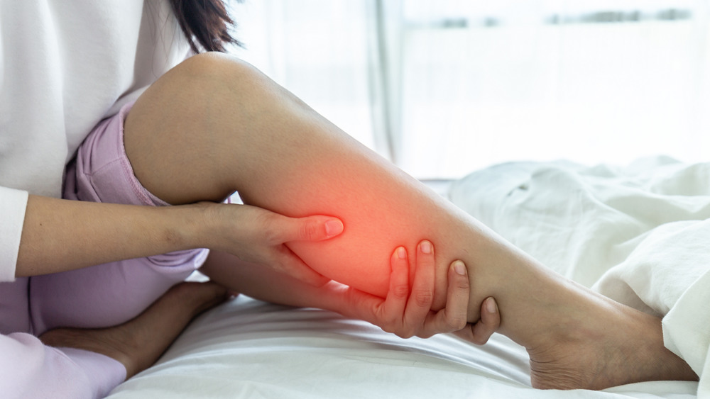 Woman in pain holding calf muscle