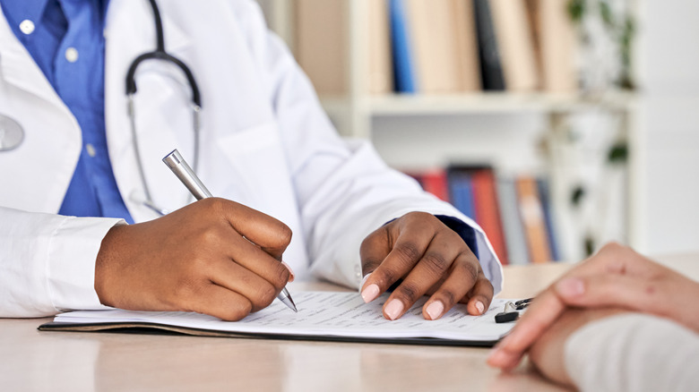 Medical doctor's clipboard and patient's hands
