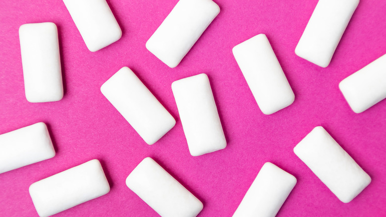 Pieces of sugar-free gum on pink background