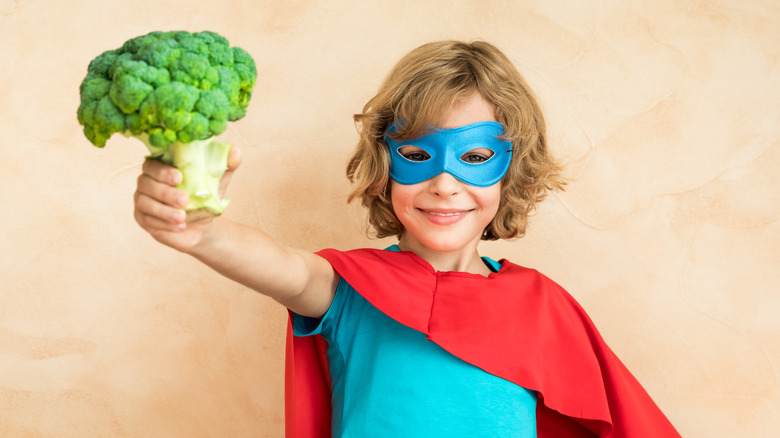 boy with mask holding broccoli