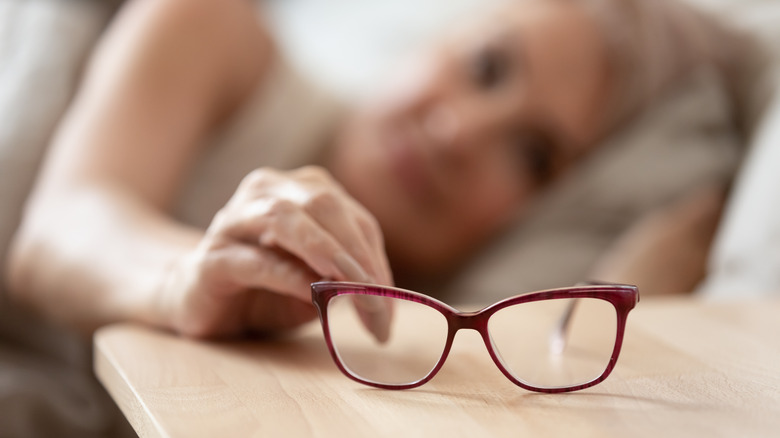 Older woman reaching for eye glasses on nightstand
