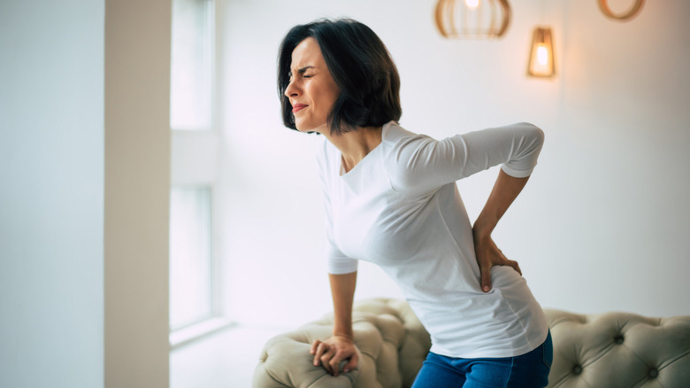 A woman holds her lower back in pain