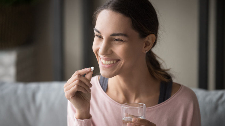 A woman is taking vitamins at home