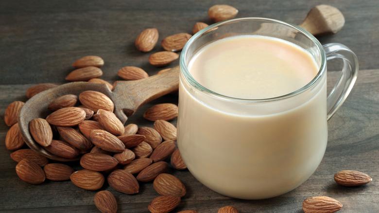 Glass of almond milk with almonds next to it