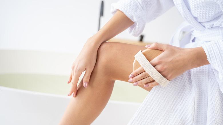 woman dry brushing thigh