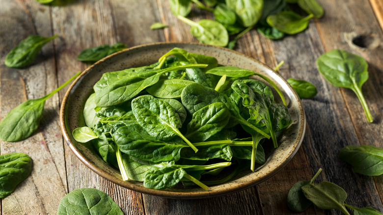 bowl of baby spinach on wooden table