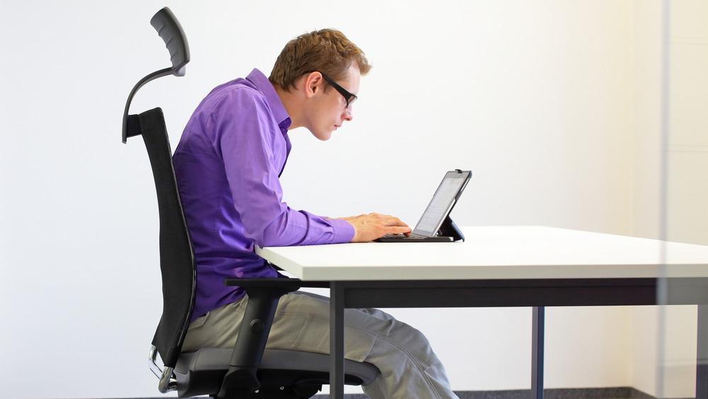 man slouching on computer