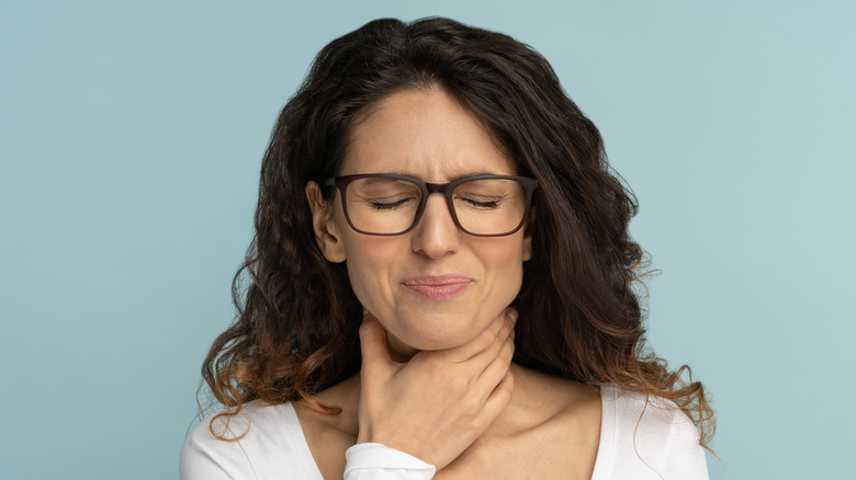 Young woman with glasses holding her throat in pain