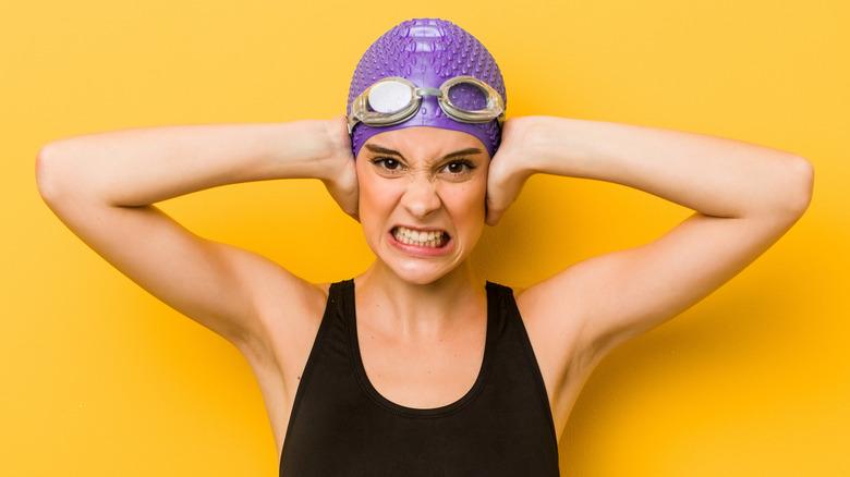 female swimmer holding her ears
