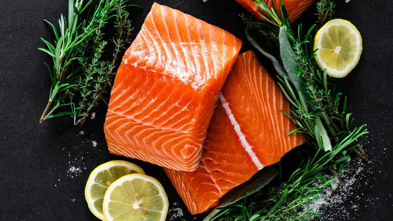 Salmon with lemon and herbs on black background