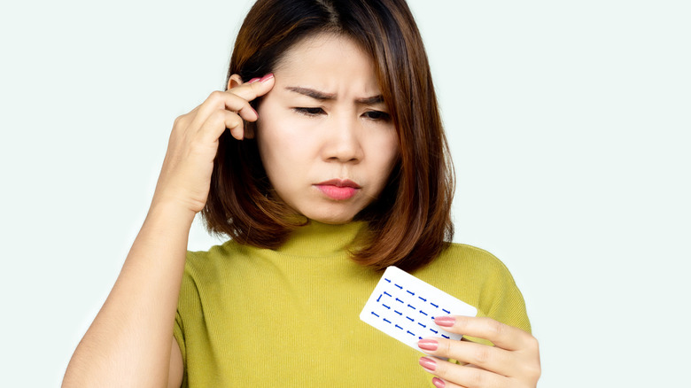 Woman looking confused holding birth control pill pack
