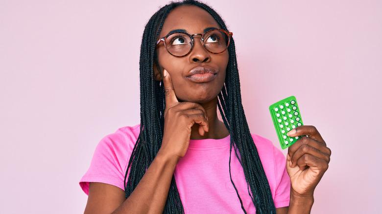 Perplexed woman holding birth control pills