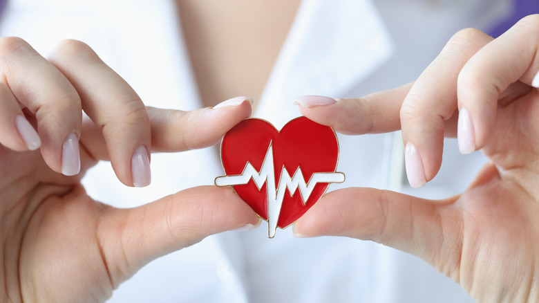 doctor holding red heart decal with electrical impulses