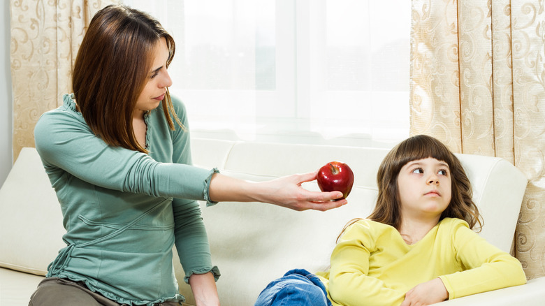 A mom tries to get her daughter to eat an apple