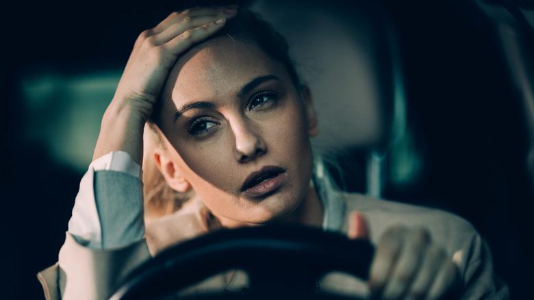 Tired woman driving car at night