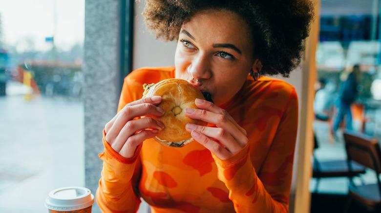 A woman eats a bagel in a coffee shop