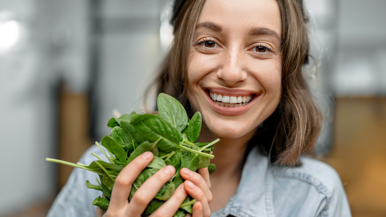 woman holding raw spinach leaves