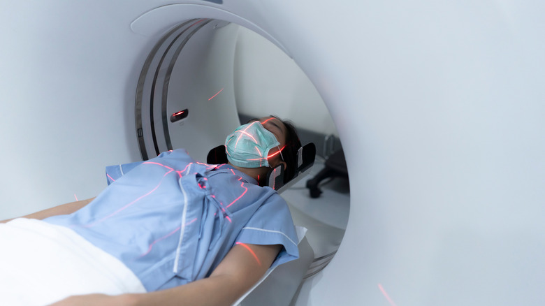 Person lies in CT scanning machine with red laser lines on her body that help technicians line her body up correctly for imaging
