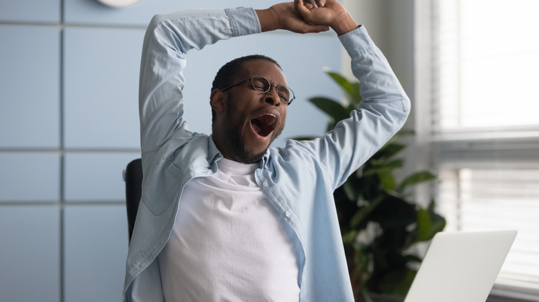 Man in glasses yawning while working at a computer