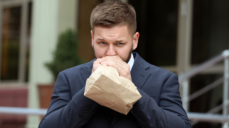 Businessman breathing into a paper bag outside