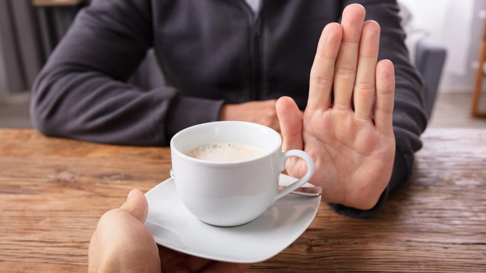 man's hand refusing coffee