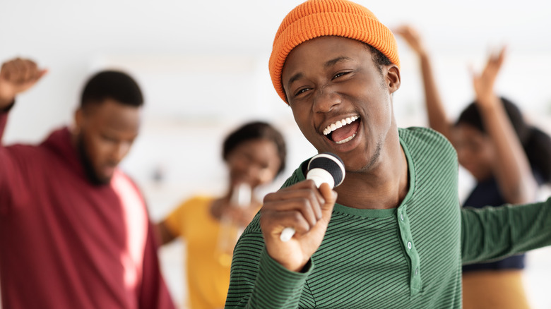 Young man singing into a microphone and dancing with friends