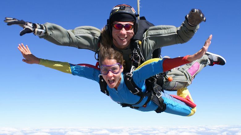 Woman skydiving strapped to male instructor