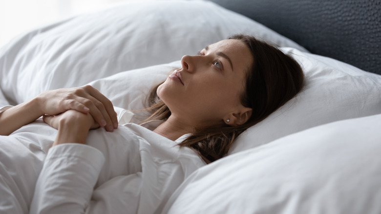 Side view of a woman lying in bed wide awake