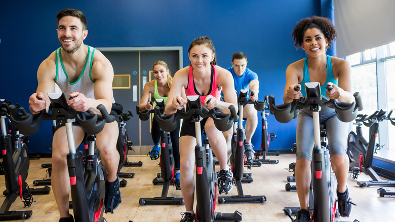 Five people taking a spin class in a room with a blue wall and windows