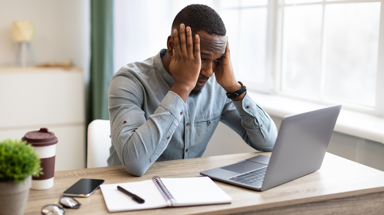 Man sitting at his laptop, holding his head because he's stressed