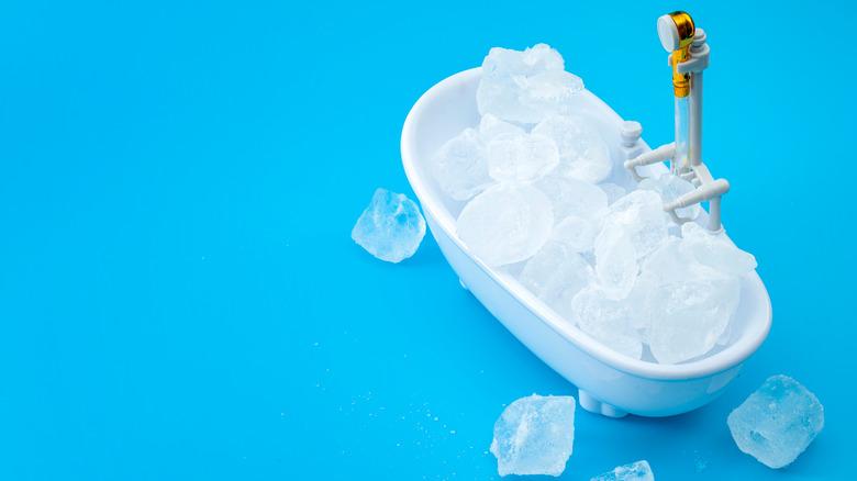 Bathtub full of ice cubes on blue background