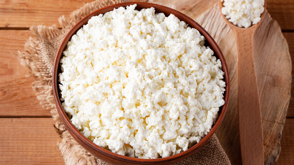 A wooden bowl full of cottage cheese