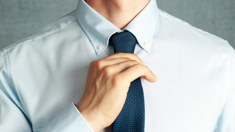 Close-up of hand adjusting necktie