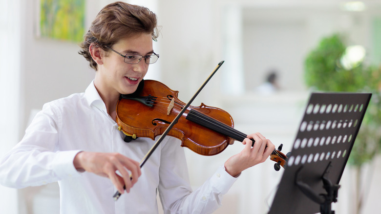 Young man playing the violin while reading music