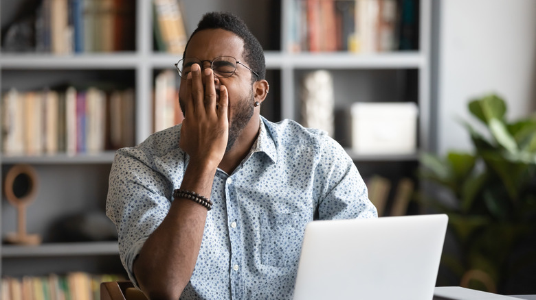 A man yawning at his computer during the day