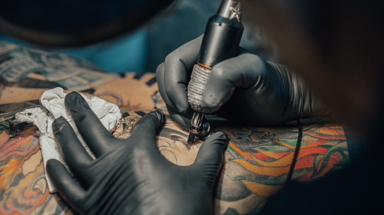 Gloved hands giving someone a tattoo