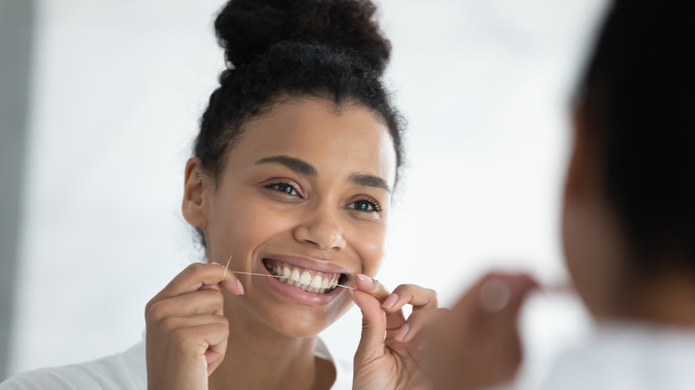 Woman flossing in front of mirror