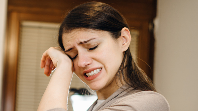 Woman rubbing eye while cooking in kitchen