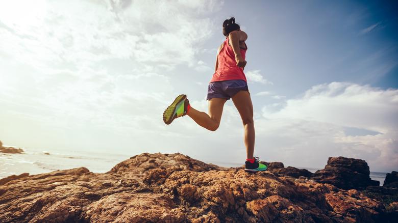 woman running along a rocky trail along the ocean