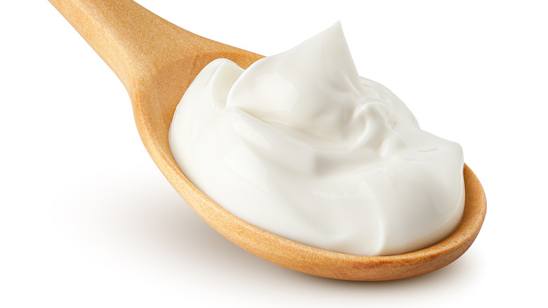 A wooden spoon full of white whipped foam