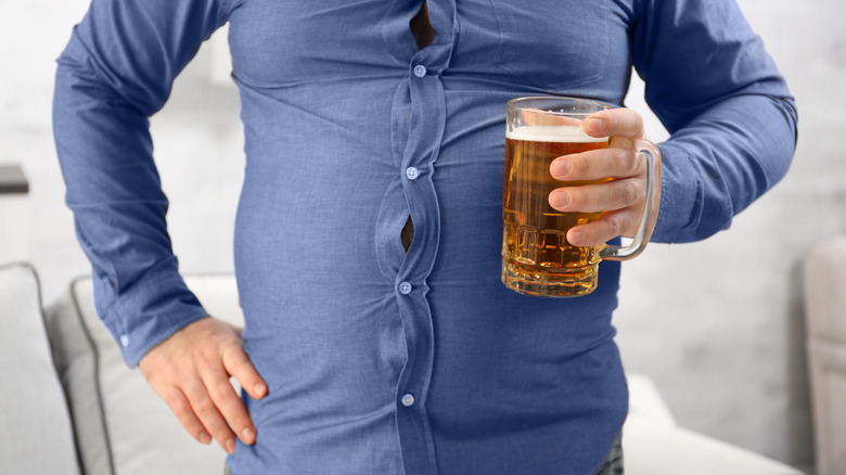 Man holding glass of beer with beer belly wearing shirt with buttons popping out