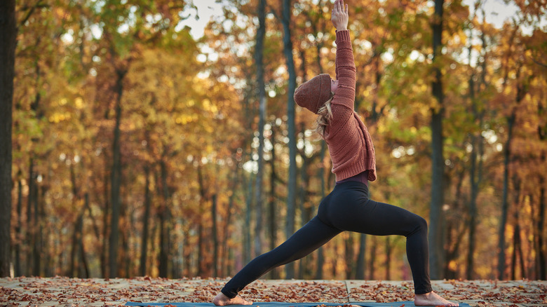 A woman does yoga outside in autumn